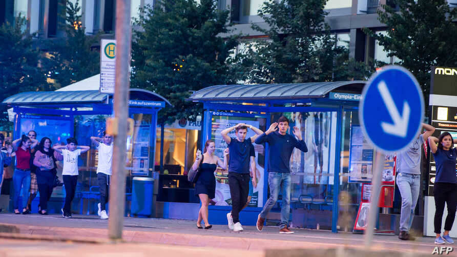 Evacuated people from the shopping mall walk with their hands up in Munich on July 22, 2016 following a shooting earlier.