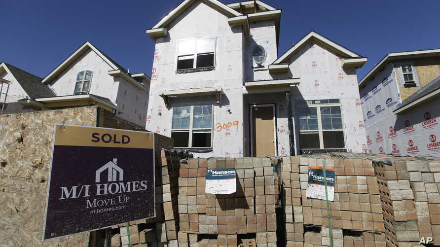 """FILE - In this Tuesday, Feb. 2, 2016, file photo, a """"Sold"""" sign sits in front of a house under the final stages of construction in Plano, Texas."""