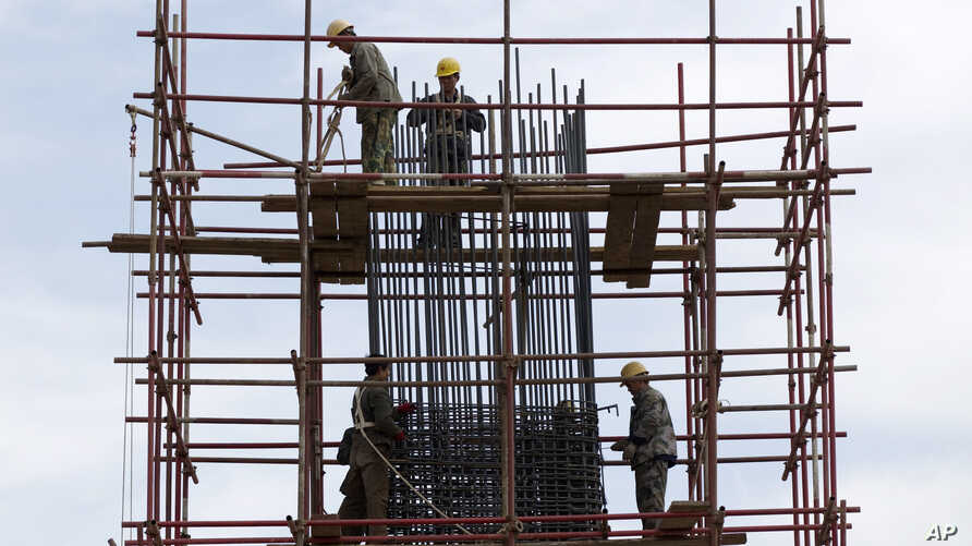 Workers stand on scaffolding at a road construction site in Beijing (April 2012 file photo).