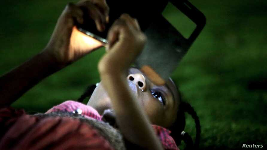 FILE - A girl uses a mobile phone in Khartoum, Sudan. In neighboring South Sudan, the government cut the signal on the Vivacell telecom firm this week, alledging it had not paid licensing fees.