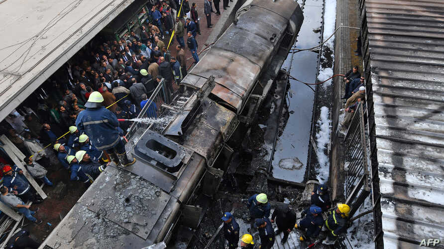 Firefighters and onlookers gather at the scene of a fiery train crash at Cairo's main railway station, Feb. 27, 2019.