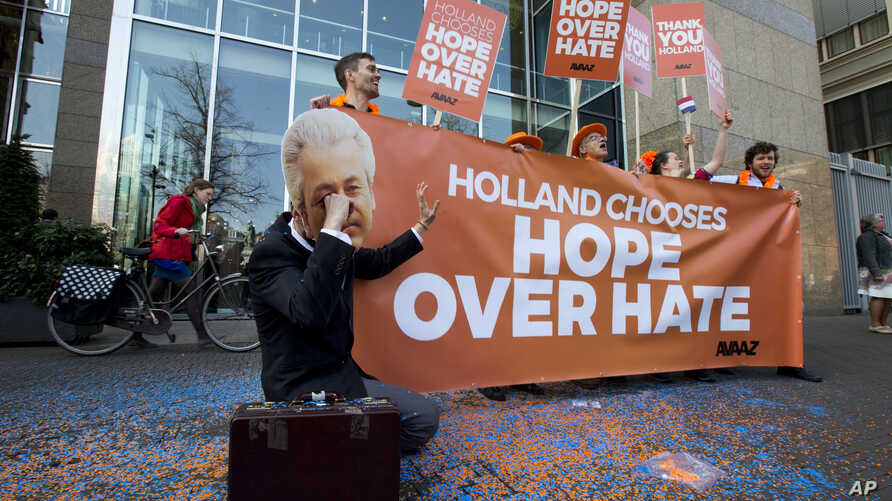 A man poses as crying firebrand anti-Islam lawmaker Geert Wilders during a small demonstration outside parliament, rear, in The Hague, Netherlands,  March 16, 2017.