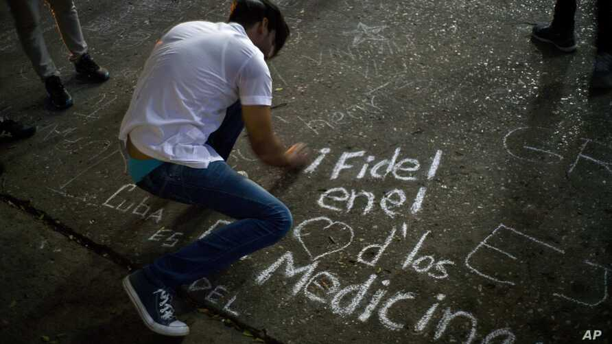 """A student writes on a sidewalk with chalk """"Fidel in the hearts of the med students"""" during a vigil for the late Cuban leader Fidel Castro at the university where Castro studied law as a young man in Havana, Cuba, Nov. 26, 2016."""