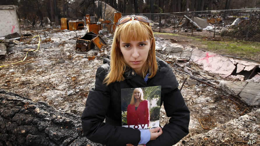 In this Thursday, Feb. 7, 2019 photo, Christina Taft, the daughter of Camp Fire victim Victoria Taft, poses with a photo of her mother, at the burned out ruins of the Paradise, Calif., home where she died last fall.