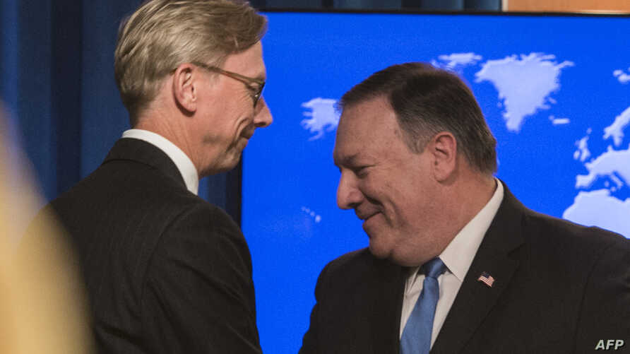"FILE - The State Department's director of policy planning and head of the Iran Action Group, Brian Hook (L), shakes hands with Secretary of State Mike Pompeo after the announcement of the ""Iran Action Group"", August 16, 2018."