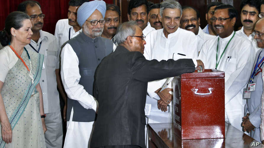 Pranab Mukherjee casts his vote in India's presidential election as PM Singh and Congress party president Sonia Gandhi, along with other lawmakers look on in New Delhi, July 19, 2012.