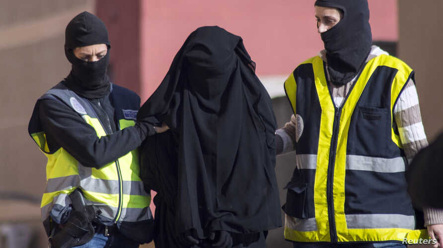 Masked Spanish police officers lead a detained woman in Melilla, December 16, 2014. Spanish and Moroccan police have arrested seven people in a ongoing joint swoop on suspected efforts to recruit women to go to Syria and Iraq to support Islamic State...