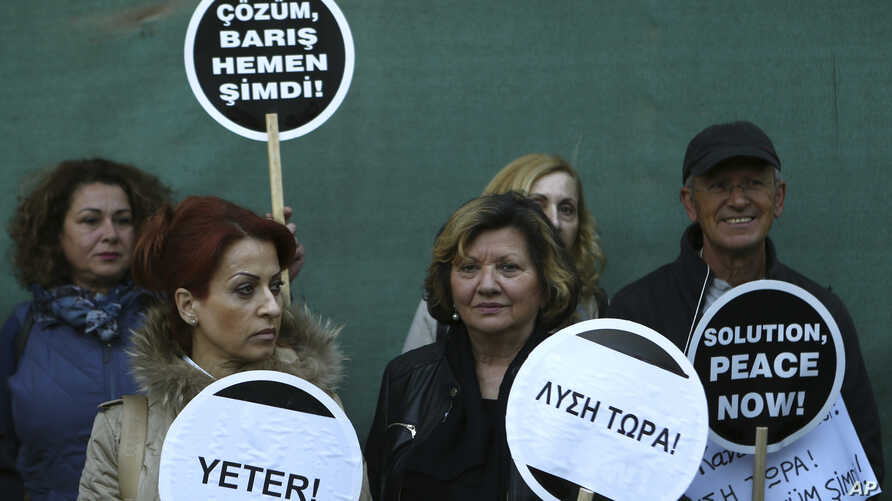 """Greek and Turkish Cypriots holds banners reading in Greek, Turkish and English """"Solution Now"""" as they stand in front of the main gate of the Ledras Palace, where the United Nations envoy will host a dinner with ethnically divided Cyprus' rival leader"""