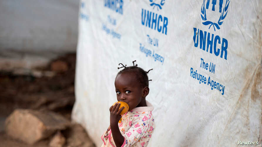 FILE - A girl eats a mango at a shelter for displaced people in Bangui, Central African Republic, April 24, 2017.