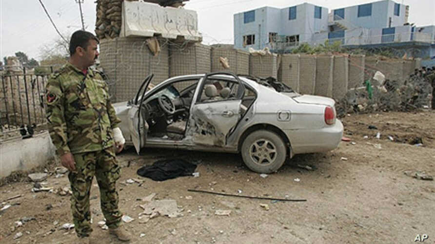 An Iraqi police commando stands next to the wreckage of a car at the site of suicide bombing in the restive city of Baquba northeast of Baghdad, 03 Mar 2010