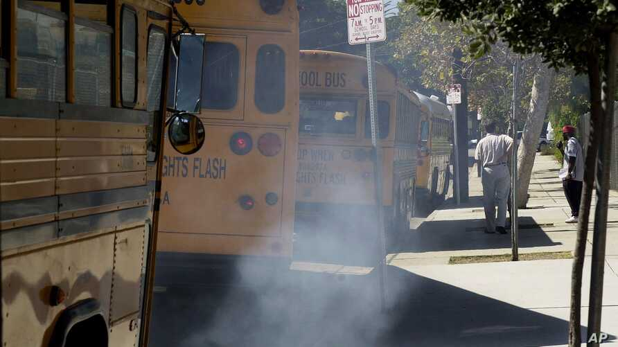 Buses spew diesel-fuel exhaust as they start up and pull away from an elementary school near Los Angeles, September. 6, 2000.