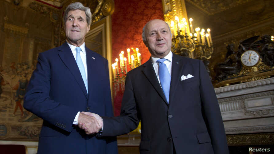 U.S. Secretary of State John Kerry (L) shakes hands with French Foreign Minister Laurent Fabius as he arrives at the Quai d'Orsay in Paris, Oct. 13, 2014.