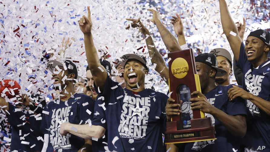 Connecticut celebrates with the championship trophy after beating Kentucky 60-54 at the NCAA Final Four tournament college basketball championship game Monday, April 7, 2014.