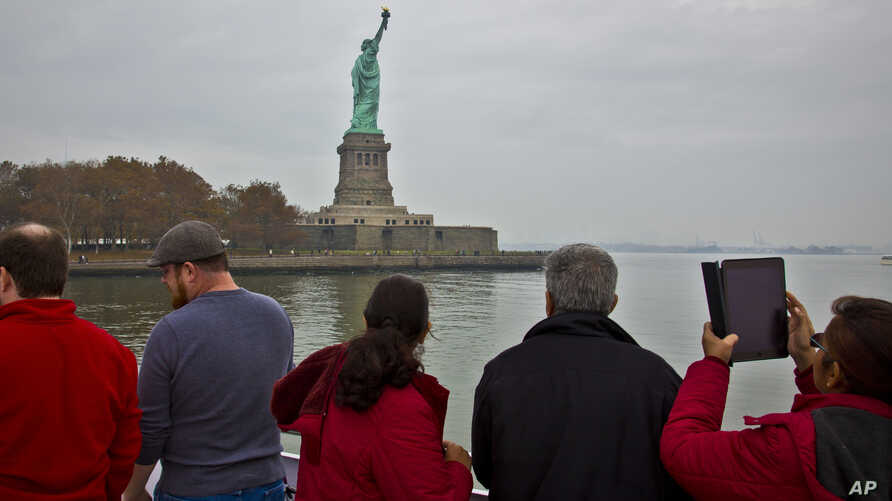 FILE - Tourists view the Statue of Liberty during a ferry ride to Liberty Island in New York, Nov. 5, 2015. A U.N. official predicts the U.S. will lose millions of dollars as tourists will shun the country due to the Trump administration's controvers
