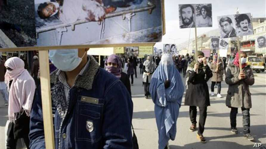 Protesters carry portraits of Afghans who were killed in the past three decades of war and violence during a demonstration for human rights, Kabul, Dec. 10, 2012.