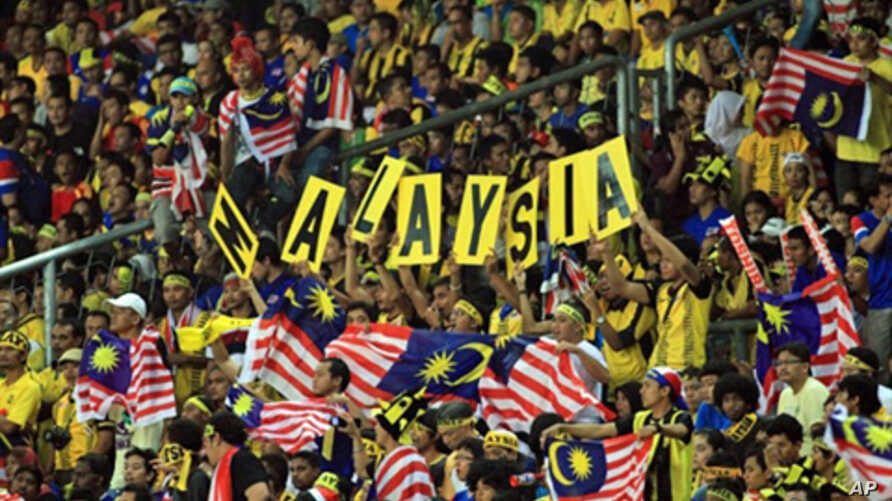 Malaysia football fans hold up national flags during the AFF Cup 2010 first leg finals football final match held at the Bukit Jalil National Stadium in Kuala Lumpur, Dec. 26, 2010.