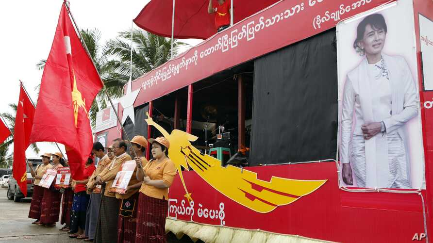 FILE - Supporters holding flags of Myanmar's opposition leader Aung San Suu Kyi's National League for Democracy party stand as a Myanmar artist sings a song on campaign truck during an election campaign in Yangon, Oct. 7, 2015.