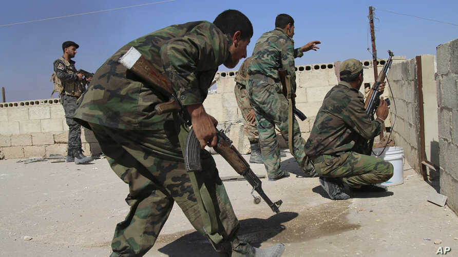 In this photo taken on Oct. 11, 2015, Syrian soldiers fire repelling an attack in Achan, Hama province, Syria