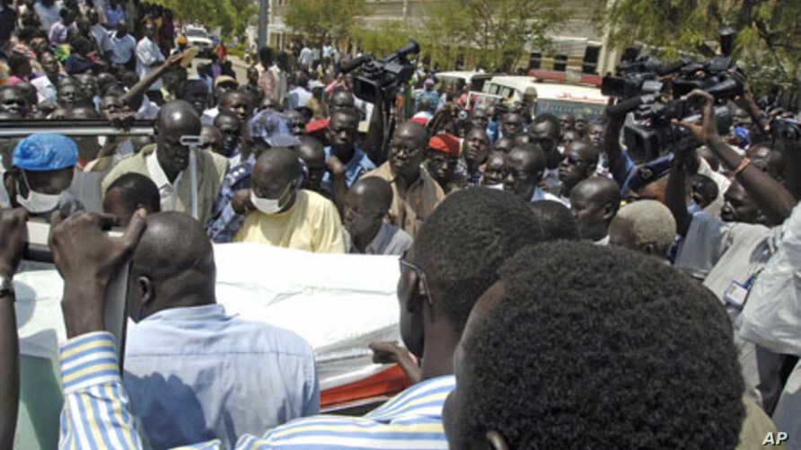Civilians carry the body of a slain police officer to an ambulance after the killing of South Sudan's Minister for Rural Development and Cooperatives Jimmy Lemi Milla at the ministry compound in Juba February 9, 2011