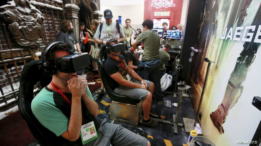 """Attendees wearing Oculus Rift virtual reality headsets view a 3-dimensional video for the """"Pacific Rim: Jaeger Pilot"""" video game during the 2014 Comic-Con International Convention in San Diego, California, July 25, 2014."""