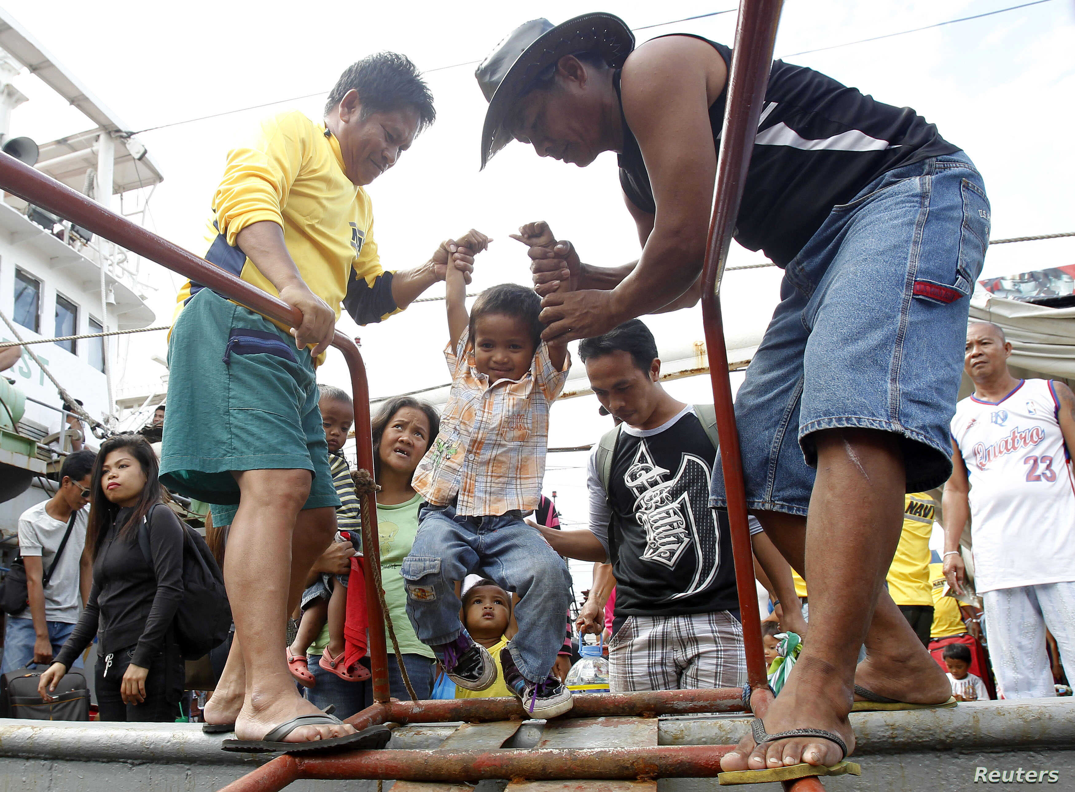 A child survivor of super Typhoon Haiyan is given assistance as he disembarks from a Philippine Navy ship upon arrival at the north harbor in Manila, Nov. 29, 2013.