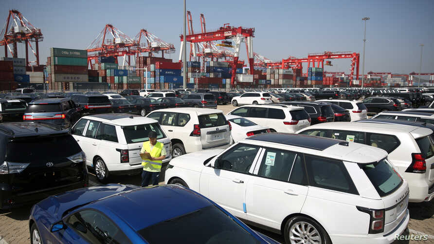 FILE - A worker inspects imported cars at a port in Qingdao, Shandong province, China, May 23, 2018.