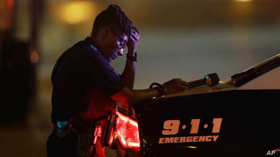 A Dallas police officer, who did not want to be identified, takes a moment as she guards an intersection in the early morning after a shooting in downtown Dallas, July 8, 2016.