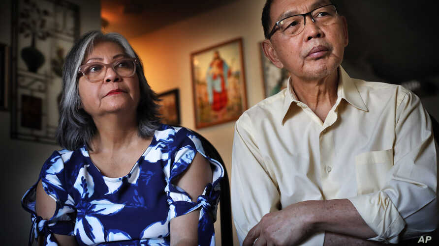 In this Dec. 1, 2017 photo, Poppy Sombah, left, and Freddy Sombah listen to an Indonesian community leader at their home in Somersworth, New Hampshire. The couple fled Indonesia to escape harassment from their Muslim neighbors following Poppy's conve