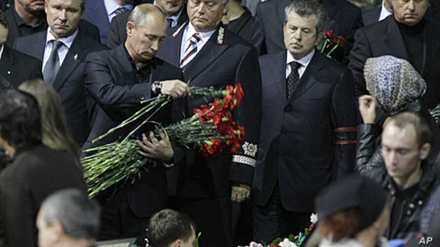 Russian Prime Minister Vladimir Putin lays flowers during a funeral service for the victims of Wednesday's plane crash, in the Arena Yaroslavl, 150 miles (240 kilometers) northeast of Moscow in Russia, Sept. 10, 2011.