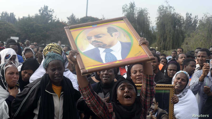 A woman wails while lifting a portrait of Ethiopia's PM Meles Zenawi as she waits for the arrival of his remains in Ethiopia's capital Addis Ababa, August 21, 2012.