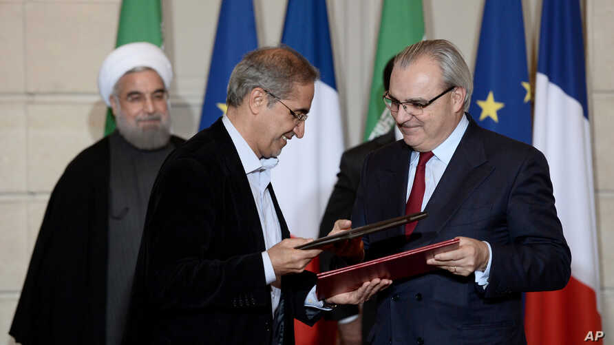 Chief Executive of Suez Environment, Jean-Louis Chaussade (R), Iranian Energy Vice-Minister, Alireza Daemi (L), Iranian President Hassan Rouhani (Background L), and French President Francois Hollande attend a bilateral agreements session in Paris, Ja