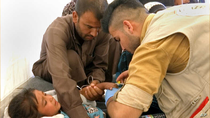 In this frame grab from video, a man comforts his daughter as a doctor treats her after she was taken ill with suspected food poisoning in the Hassan Sham U2 camp for displaced people located about 20 kilometers (13 miles) east of Mosul, Iraq, June 1