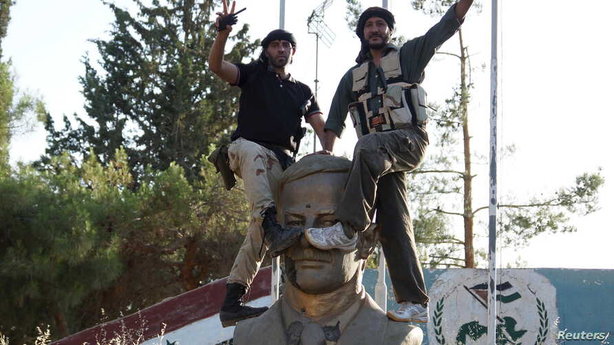 Members of the Free Syrian Army celebrate as they place their feet on a sculpture of late Syrian President Hafez al-Assad, father of Syrian President Bashar al-Assad, at the Brigade 52 military base in Daraa, Syria, June 9, 2015.