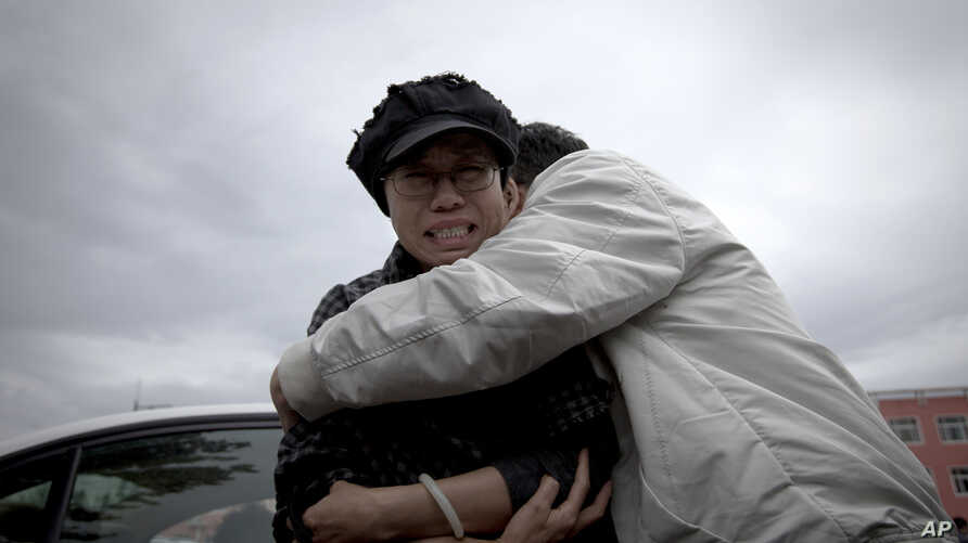A relative comforts Liu Xia, left, wife of imprisoned Nobel Peace Prize winner Liu Xiaobo, while she cries outside Huairou Detention Center where her brother Liu Hui has been jailed in Huairou district, on the outskirts of Beijing, China, June 9, 201