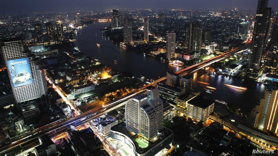 FILE - Cars and trains move on Taksin bridge over Chao Phraya river in central Bangkok, Thailand, at sunset, March 14, 2013.