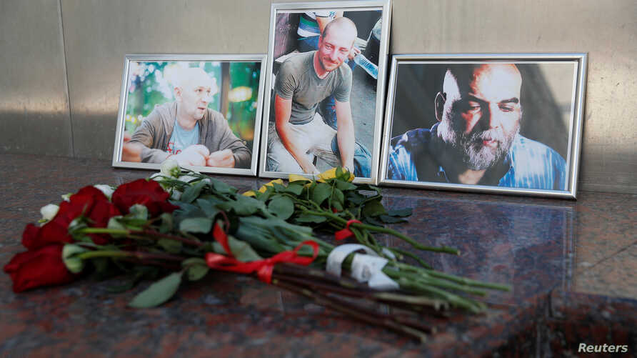 Photographs of journalists, (R-L) Orhan Dzhemal, Kirill Radchenko and Alexander Rastorguyev, who were recently killed in Central African Republic by unidentified assailants, are on display outside the Central House of Journalists in Moscow, Aug. 1, 2