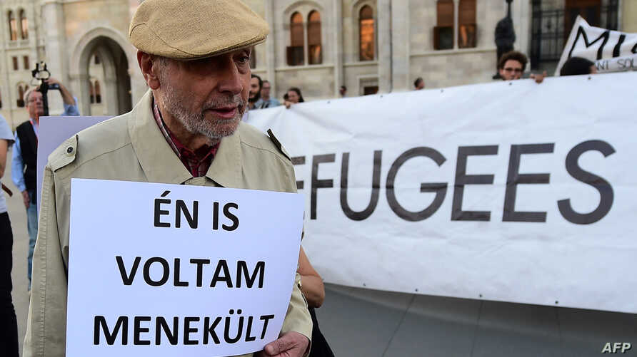 """An elderly man walks with his placard with text, """"I was refugee also,"""" as activists hold up a banner with 'Refugees welcome' during protests against the migration policy of the Orban government in front of the parliament building in Budapest, Sept. 3"""