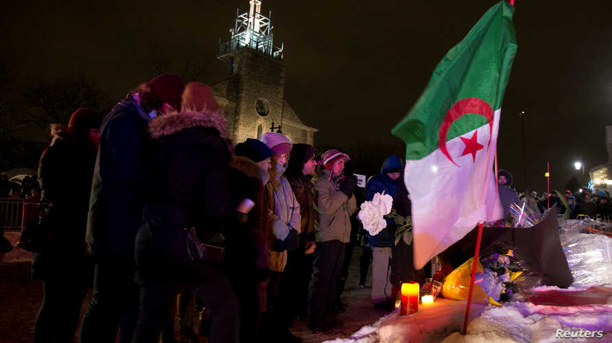 People pay respects at a make-shift memorial following a vigil held in honor of the victims of a shooting in a mosque in Quebec City, Canada, Jan. 30, 2017.