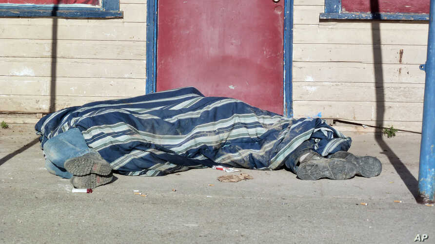 In this Aug. 9, 2013, photo homeless people cover themselves with a blanket on a street in Whiteclay, Neb. Many tribal members live on the tiny town's barren streets to avoid arrest on the nearby reservation for being intoxicated..