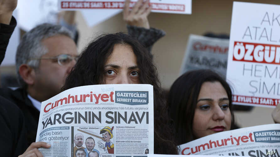 Demonstrators hold placards and copies of the Cumhuriyet daily newspaper as they stage a protest outside a court where the trial of about a dozen employees of the newspaper on charges of aiding terror groups, continues in Istanbul, Oct. 31, 2017.