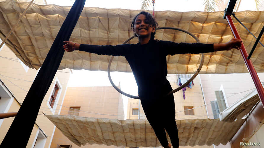 "A girl performs with hanging hoops during a training session at al-Darb al-Ahmar Arts School ""DAAS"" where children learn circus skills and arts in old Cairo, Egypt, July 17, 2018."