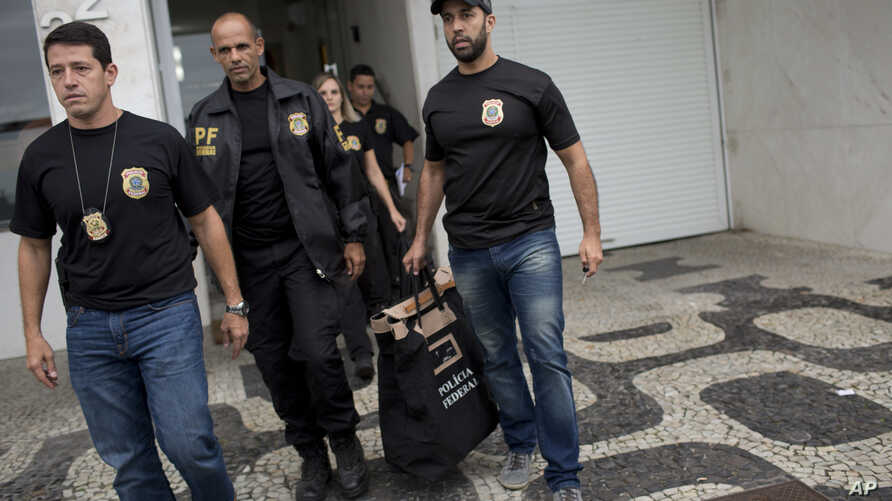 Federal police officers leave the building where Brazilian Sen. Aecio Neves resides, at Ipanema beach in Rio de Janeiro, Brazil, May 18, 2017.