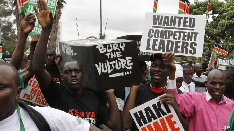 Youth groups protestors carrying replicas of 49 coffins saying bury the vulture seen in Nairobi, Kenya,June 28, 2012.