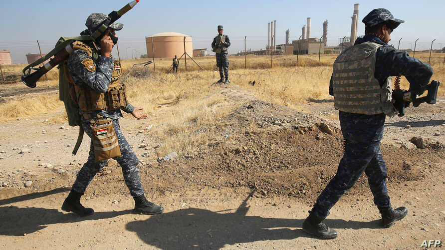 Iraqi forces walk past an oil production plant as they head towards the city of Kirkuk during an operation against Kurdish fighters on Oct. 16, 2017.