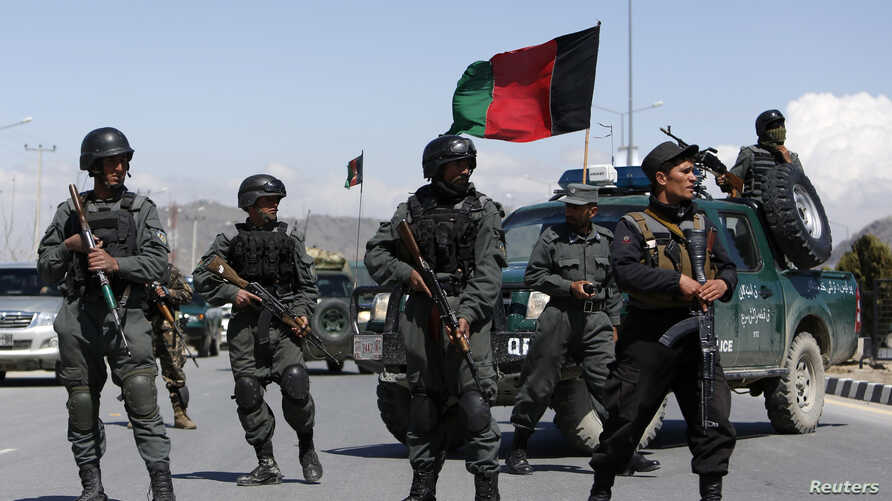 Afghan policemen stand guard near the site of an attack in Kabul, March 25, 2014.