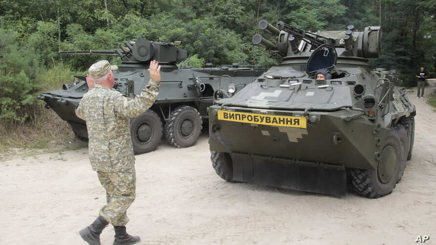 FILE - Ukrainian armored military vehicle BTR 3E takes position prior to a test firing at the shooting range of the Kiev's armored plant, in Kyiv,Ukraine.