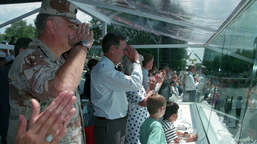 FILE - General Norman Schwarzkopf and U.S. President George H.W. Bush salute troops passing the presidential reviewing stand during Desert Storm Victory parade in Washington, June 8, 1991. The parade was held after the war against Iraq.