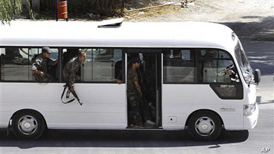 In this citizen journalism image, Syrian security forces lean out of a bus windows as they withdraw from the Damascus suburb of Saqba, Syria,  following a campaign of raids and arrests that are part of a nationwide crackdown against protesters callin