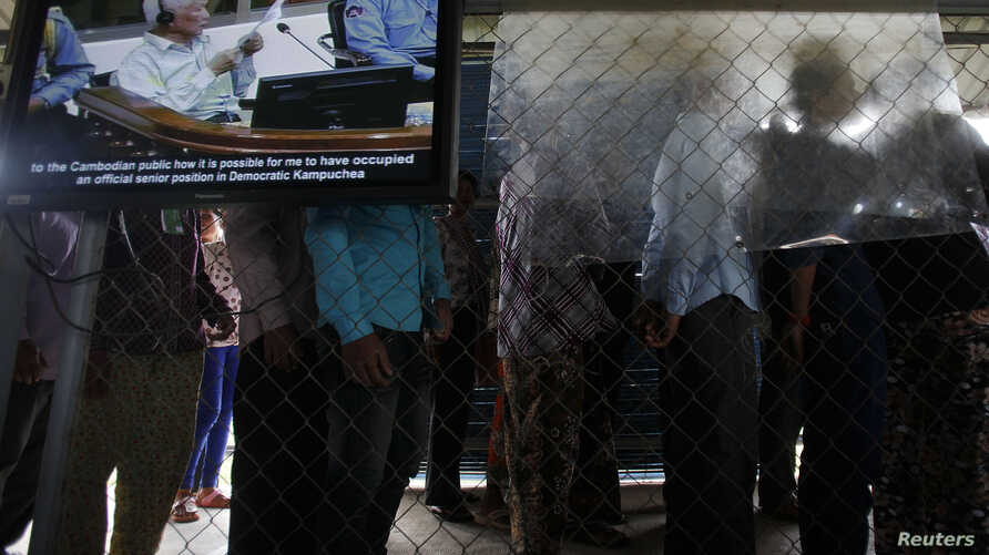 FILE - People line up to enter the Extraordinary Chambers in the Courts of Cambodia (ECCC) as a television screen shows former Khmer Rouge president Khieu Samphan, in the outskirts of Phnom Penh.