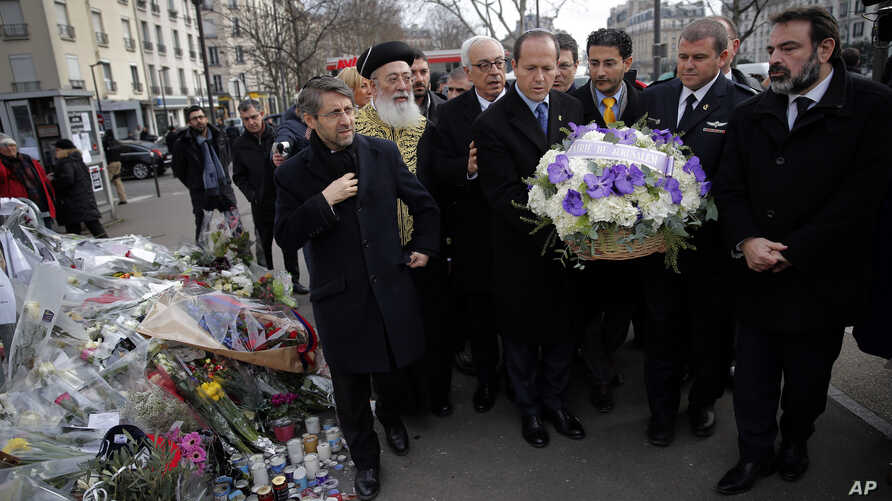 Jerusalem Mayor Nir Barkat, center, and Israeli Chief Rabbi Shlomo Amar, second left,  lay a wreath of flowers at the kosher grocery where Amedy Coulibaly killed four people in a terror attack, in Paris, Wednesday, Jan. 21, 2015.